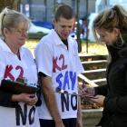 Dunedin resident Samantha Hill (23) signs a petition in the Octagon yesterday, to aid a campaign...