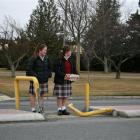 Dunstan High School year 10 pupils Erin Calder (14, left) and Meg McCone (15) cross the busy...