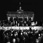 East and West German citizens celebrate as they climb the Berlin wall at the Brandenburg gate...