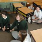 East Otago High School pupils sit on the floor and stay away from windows, as directed, during...