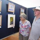 Eileen and Michael Ferns, of Invercargill, contemplate landscape paintings by Graeme Bell and...