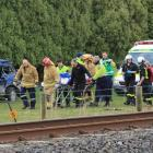 Emergency services carry the driver to the Otago Regional Rescue Helicopter at the crash scene...