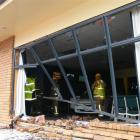 Emergency services personnel inspect the damage after a car reversed into the Gore and Districts...