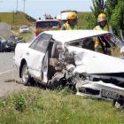 Emergency services personnel survey the scene of a three-car crash near Totara yesterday...