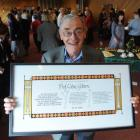 Emeritus Prof Colin Gibson displays the 2010 Library Citation he received from the Dunedin Public...