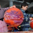 Emma Small (4) and  brother Sean (6) transform paper lamp shades into Venus-like orange planetary...