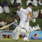 England's Alastair Cook and Jonathan Trott (L) cross for a run during the second test against...