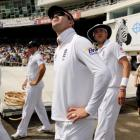 England's Kevin Pietersen (3rd L) and Stuart Broad (4th L) look up as the players prepare to walk...