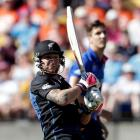 England's Steven Finn (right) watches as another of his deliveries is hit to the boundary by...
