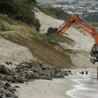 A digger repairs some of the damage on Dunedin's St Clair beach near Moana Rua Rd after heavy...