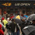 Fans wait near playing courts after rain delayed competition in the US Open in New York. Photo:...