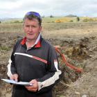 Farmer Jim Thomson reads a Chorus quote as he stands in the trench dug on his East Otago farm....
