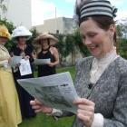 Fashion-in-the-field contender Tania Pacey reads a souvenir copy of the racing edition of The...