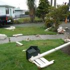 Fence palings and broken bricks landed on the front lawn of the Odell family's property in...