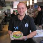 Fergburger general manager Barry Smith holds a specially adorned burger in a rare, less hectic...