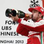 Ferrari driver Fernando Alonso of Spain drinks champagne as he celebrates winning the Chinese F1...