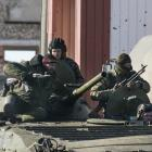Fighters with separatist self-proclaimed Donetsk People's Republic army sit on top of a moving...