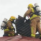 Fire crews remove roofing to ventilate a house after it caught fire  in Milton yesterday.  Photo...