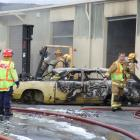 Fire crews used breathing apparatus while extinguishing a fire which started in this wrecked car ...