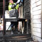 Fire safety officer Barry Gibson checks the wiring at a badly damaged house in Millers Flat after...