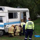 Fire Service personnel check a damaged camper van at the north end of Lake Hayes last night after...