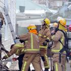 Firefighters at the scene of a house fire at Richmond St, Forbury, on Sunday evening.  Photo by...