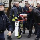 Firefighters carry a victim on a stretcher at the scene after a shooting at the Paris offices of...