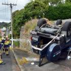 Firefighters clean up an oil spill from a truck which rolled over a bank in Sydney St, Caversham,...