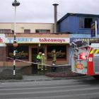 Firefighters contemplate the damage to two Oamaru takeaways restaurants, the Turret (left) and...