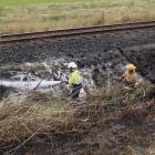 Firefighters dampen down a grass fire beside railway tracks near Henley. Photo by Craig Baxter.