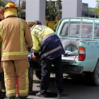 Firefighters examine the ute damaged by fire at the Invercargill Pak'n  Save fuel facility...
