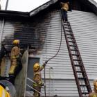 Firefighters  from Dunedin Central and Willowbank extinguish the fire yesterday. Photos by...