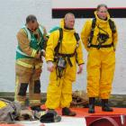 Firefighters (from left) Murray Little, Phillip De Rooy and Colin Aicken don protective suits...