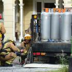 Firefighters monitor the temperature under an LPG delivery truck after it caught fire in Great...