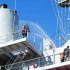Firefighters pour water on an imaginary fire on board HMNZS Endeavour during an exercise in...