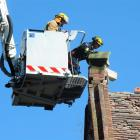 Firefighters remove loose bricks from the top of a heritage building inside the central...