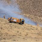 Firefighters spray water on one section of a  the grass fire near Tarras yesterday.Photos by...