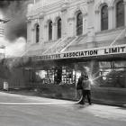 Firefighters tackle the 1969 Farmers Co-operative department store fire in Oamaru. Photo supplied.