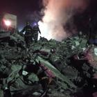 Firemen walk on the debris after an explosion at the Guomin Coal Mine in Yichuan county, in...