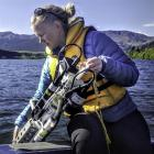 Fish & Game officer and masters student Helen Keeling, of Dunedin, lowers a water quality...