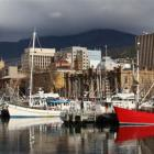 Fishing boats and pleasure craft are moored at Constitution Dock in Hobart. Flanked by both...