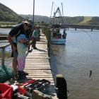 Fishing from the wharf at Taieri Mouth. On today's ride, you will pass the wharf before crossing...