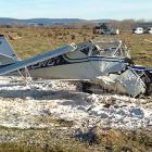 Foam covers the wreckage of a light aircraft which had engine trouble shortly after taking off...