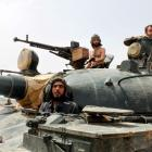 Forces of Syrian President Bashar al-Assad sit in an armoured vehicle in Qusair village near the...