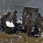 Foreign troops carry a casualty from the site of the suicide attack in Kabul.  REUTERS/Omar Sobhani