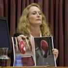 Forensic scientist Dr Anna Sandiford displays photos of bloodied feet at the Bain retrial yesterday.