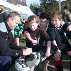 Former All Black fullback Christian Cullen (left) signs 10-year-old Chan Cowan's shoe, watched by...