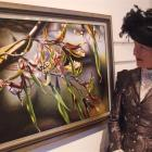 Forrester Gallery curator Else Mackenzie admires a painting of flax flowers by Barry Walsh. Photo...