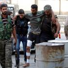 Free Syrian Army fighters help a wounded fellow fighter in Aleppo's al-Zebdieh district. REUTERS...