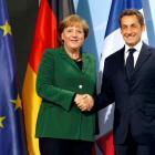 French President Nicolas Sarkozy (R) and German Chancellor Angela Merkel shake hands after...